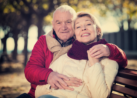 Aged husband and wife sitting together on bench in park on chilly day Stock Photo