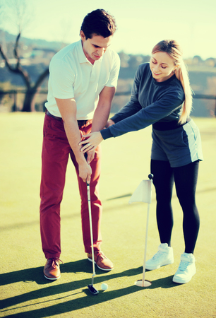 Beautiful golf trainer showing male player how to hit ball rightly