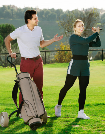 brassy: Man 30-35 years old is showing woman 25-29 years old to play golf and hit ball correctly.