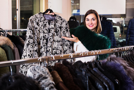acquiring: Positive girl deciding on warm fur jacket in women�s cloths store Stock Photo