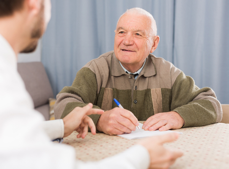 Senior man preparing agreement papers with social worker at home