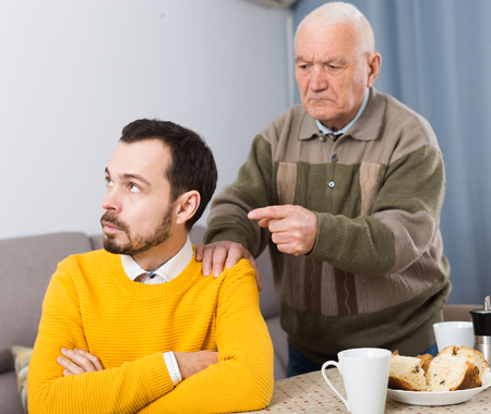 eldest: Elderly father talking seriously and instructs his son at home Stock Photo