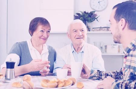 Elderly grandparents having breakfast with grandson sitting at table