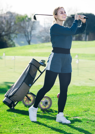 happy woman golfer propelled ball successfully at golf course Stock Photo