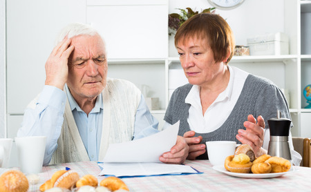 accounts payable: Elderly couple studying agreement conditions before signing at home Stock Photo
