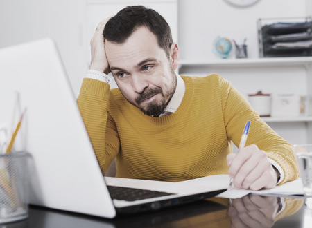 compile: Man at desk at office makes important documents on notebook Stock Photo