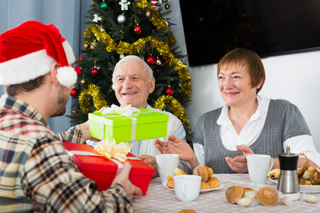 Old couple get gifts from grandson for Christmas and Happy New Year