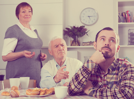 disagreeing: Father and mother having disagreement with adult son at home