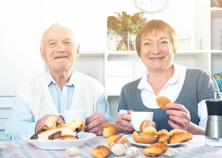 Smiling elderly couple having breakfast and talking at table at home Imagens