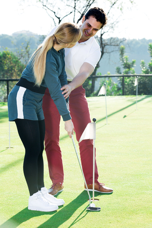 Happy male golf trainer showing female player how to hit ball rightly
