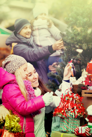 5s: Family with children purchasing the Christmas decoration and souvenirs at a fair. Focus on women Stock Photo