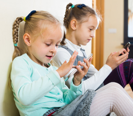 Two little girls 6-8 years old playing with smartphones at home Stock Photo