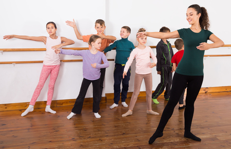 assiduous: assiduous boys and girls primary school age rehearsing ballet dance in studio Stock Photo