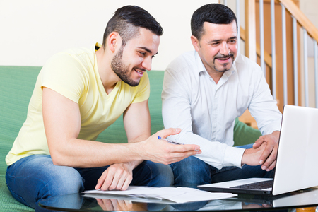 the elderly tutor: Smiling insurance agent giving presentation to a positive client at home