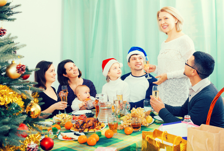granny and grandad: family with children celebrates Christmas at table in home