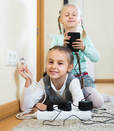 Careless american children playing with sockets and electricity indoors