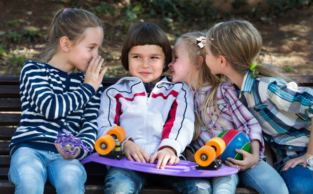 blabbing: Cheerful smiling  little boy and girls sharing secrets as talking outdoor