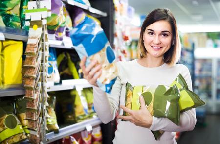 スーパーでおいしい軽食を選択する若いロシア人女性