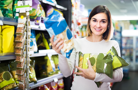 Joven mujer rusa elegir deliciosos bocadillos en el supermercado