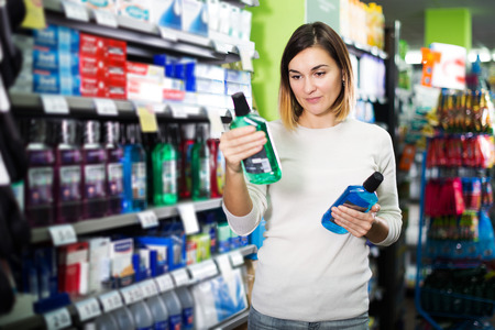Young female shopper searching for mouthwashes in supermarket Stock Photo
