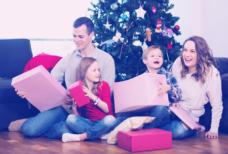 familia animada: Cheerful family members presenting gifts on Christmas at home