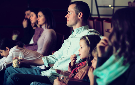captivated: Audience eating popcorn and enjoy watching movie in the cinema