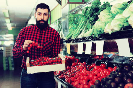 Smiling male seller offering tomatoes in grocery shop
