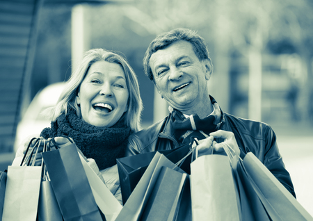Cheerful pleasant positive mature spouses with shopping bags in spring day