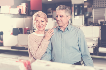 Mature couple are visiting shop of household appliances for buying goods for kitchen and house.