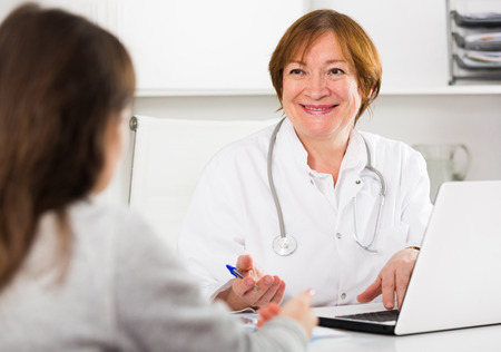 Young woman having consultation with female doctor in hospital Stock Photo