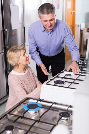 gas stove: happy mature couple chooses in shop of household appliances gas stove with oven to itself home Stock Photo