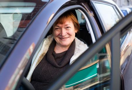 75s: Portrait of happy european female senior driver smiling in car