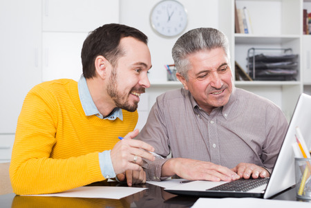 Smiling adult and young employees looking at interesting on Internet at computer