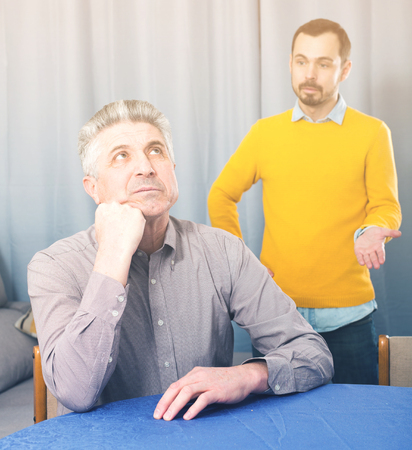 Son defends his position before adult father at home Stock Photo