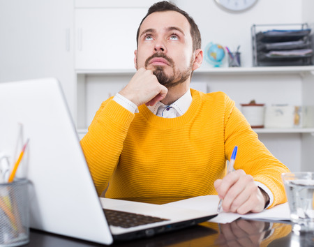 Young male student having complicated issue at online courses at home Stock Photo