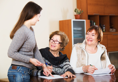 75s: Portrait of positive senior women with papers and agency employee