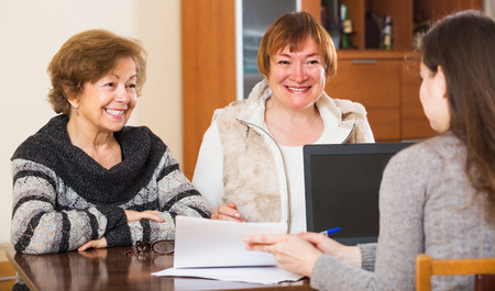 75s: Young agent consulting cheerful elderly women in office
