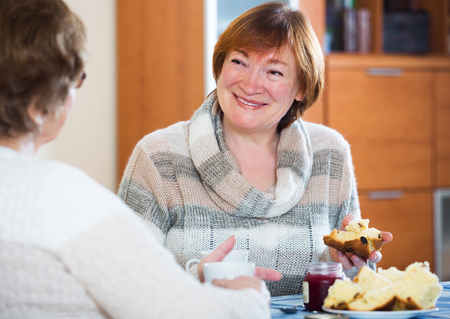Positive mature women sitting at table and chatting Stock Photo