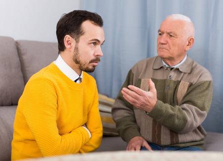 Elderly father and his son are serious conversation at home and solve problems