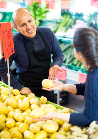 Portrait friendly worker selling vegetables to female customer Stock Photo