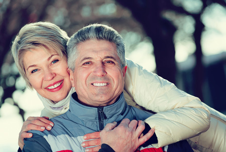 Ordinary husband and wife warmly embracing and resting together outdoors Stock Photo