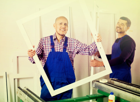 Two friendly smiling workmen in coverall with different PVC windows and doors
