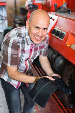 Professional efficient craftsman polishing footwear on machine in shoe atelier Stock Photo