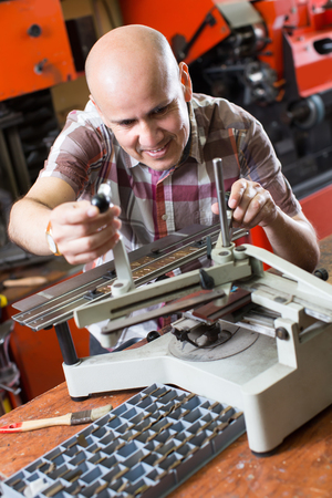 Positive smiling mature workman doing mailbox plate on machine in workshop