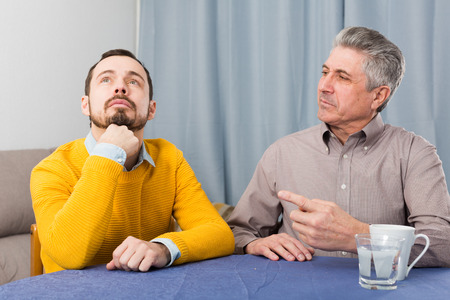 Mature father and son is serious conversation at table at home Stock Photo