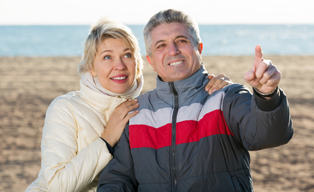 attract attention: Happy mature couple walks outdoors and point by hand to interesting objects Stock Photo