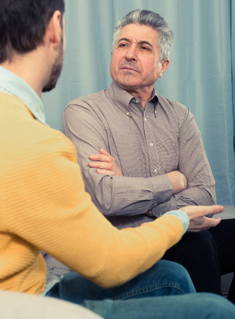Mature father and son discuss family problems and solve relationship problems Stock Photo