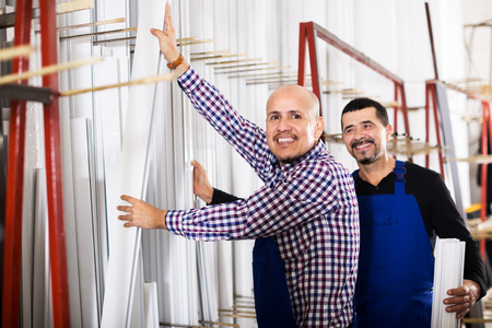 Two careful men in uniform inspecting PVC manufacturing output in workshop Stock Photo