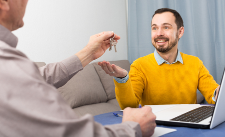 Adult man and agent sign contract of rent apartments and hand over keys 版權商用圖片