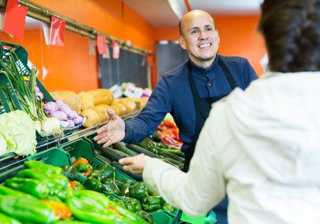 Charming salesman serving female purchasing veggies in supermarket